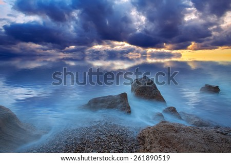 Dramatic sea sunset. Storm clouds over the stony shore. natural composition - stock photo