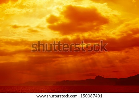 Dramatic   sea with sun rays and clouds in golden orange  colors