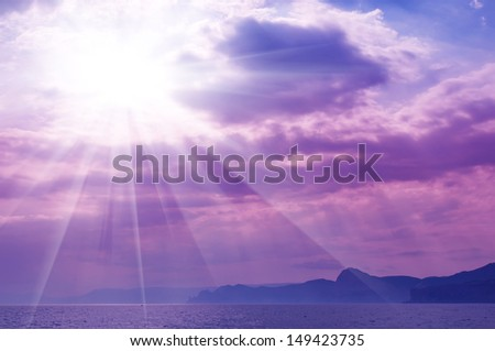 Dramatic   sea with sun rays and clouds in pink colors - stock photo