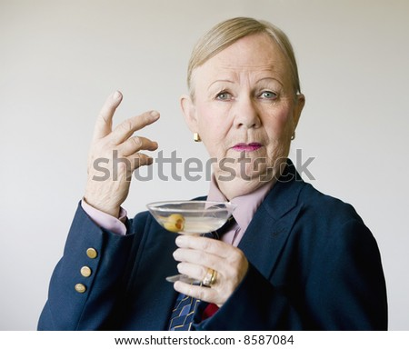 Dramatic senior woman in a man's suit holding a Martini.