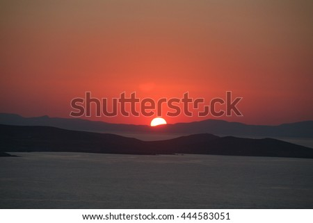 Dramatic setting sun. The setting sun over ancient Delos  viewed from Mykonos Greece