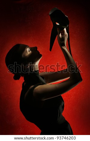 Dramatic silhouette of a beautiful woman holding a mask in front of red velvet background - stock photo
