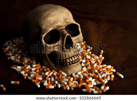 Dramatic skull in the pile of drugs symbolises sickness and danger of abuse - stock photo