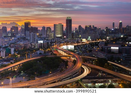 Dramatic sky after sunset over highway intersection and city downtown background - stock photo