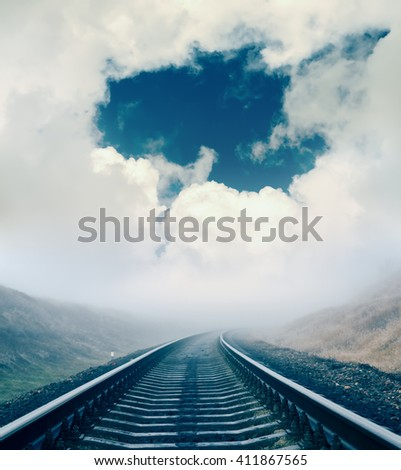 dramatic sky and railroad in fog to horizon - stock photo