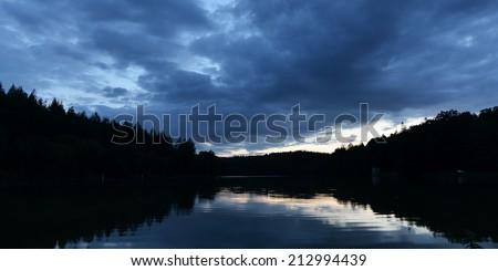 Dramatic Sky over a Lake at Dusk - stock photo