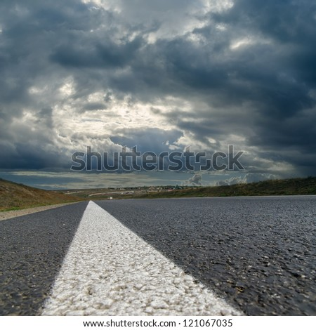 dramatic sky over asphalt road - stock photo