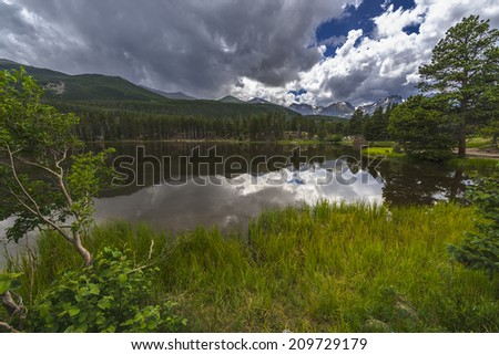 Dramatic sky over beautiful Sprague Lake with view of the Continental Divide -Colorado  - stock photo