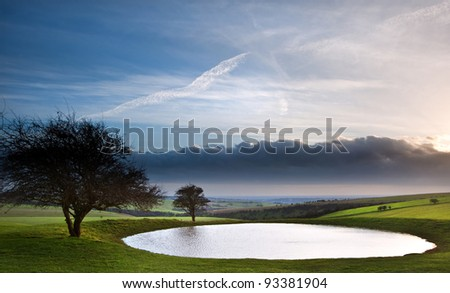 Dramatic sky over countryside landscape with naturally formed dew pond in foreground - stock photo