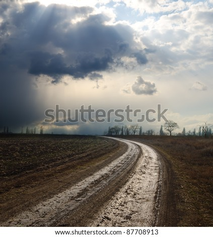 dramatic sky over field with dirty road - stock photo