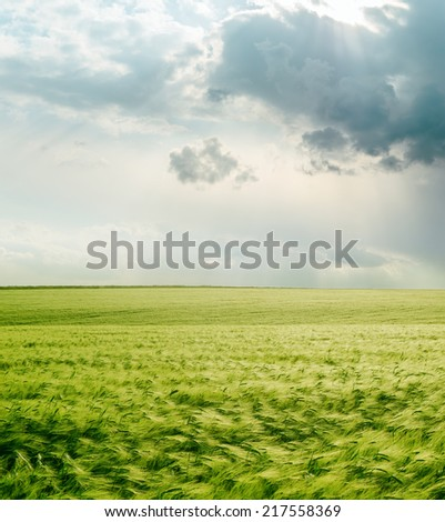 dramatic sky over green field - stock photo