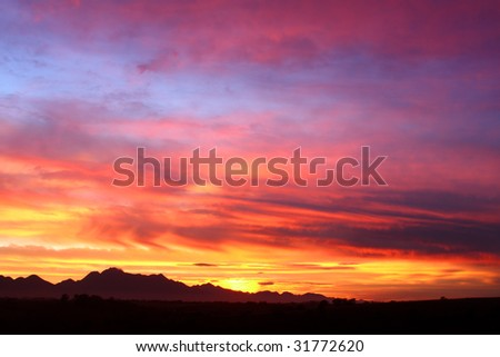 Dramatic sky over mountain silhouette - stock photo