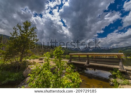 Dramatic sky over Sprague Lake trail with view of the Continental Divid Rockies Colorado - stock photo