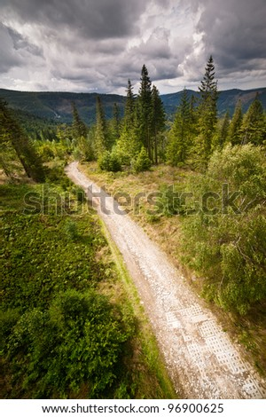 Dramatic sky over the road in mountains - stock photo