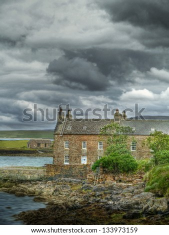 dramatic sky over typical Scottish house - stock photo