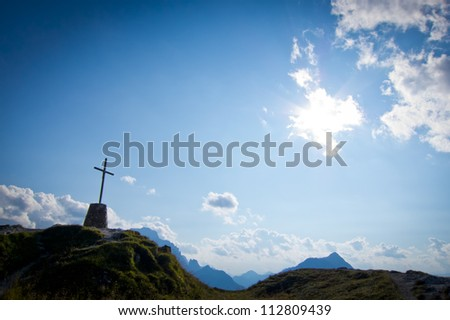 Dramatic sky scenery with a mountain cross - stock photo