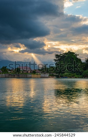 Dramatic sky, storm clouds and sun rays glowing lake Poso in central Sulawesi, Indonesia. - stock photo