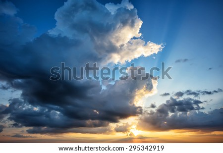 Dramatic sky with a setting sun and orange clouds - stock photo