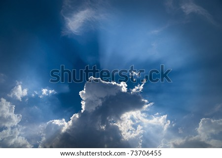 Dramatic sky with back lit clouds in blue sky - stock photo