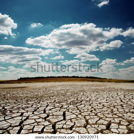 dramatic sky with clouds over cracked earth - stock photo