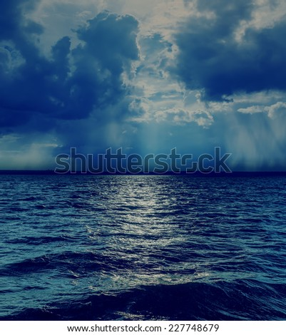 dramatic sky with clouds over dark sea - stock photo