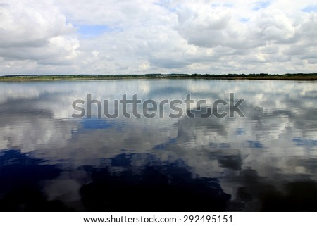 Dramatic sky with reflection in calm lake with little waves. - stock photo
