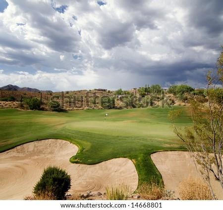 Dramatic sky with sunlight shining on beautiful desert golf course green in Scottsdale,AZ - stock photo