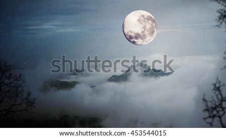 Dramatic sky with tree, full moon, fog and clouds over mountain - stock photo