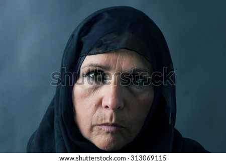 Dramatic sombre portrait of a muslim woman          - stock photo