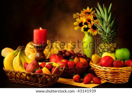 Dramatic still life of assorted fruits and garlic bread rolls - stock photo
