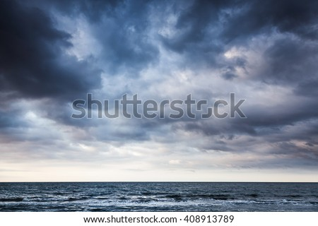 Dramatic stormy dark cloudy sky over sea, natural photo background - stock photo