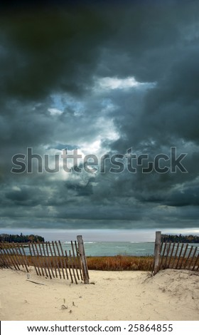 Dramatic stormy skies over a beach with a fence opening. - stock photo
