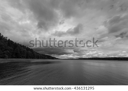 Dramatic stormy sky over lake - stock photo