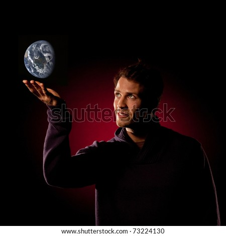 Dramatic studio shot of handsome young man holding and looking at the Earth against dark background