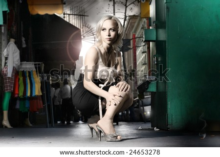 Dramatic stylized fashion portrait of female model in the city with clothing racks, mannequin and flares behind her - stock photo