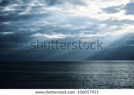 dramatic sunbeams in the sea - stock photo