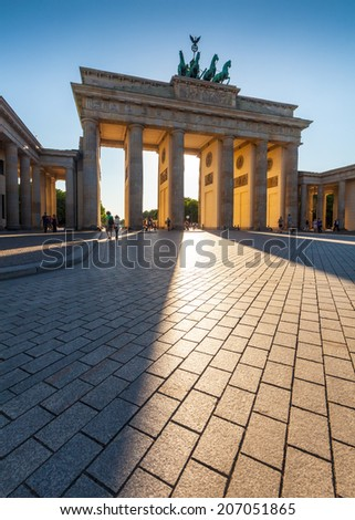 Dramatic sunlit Brandenburg Gate (1788) inspired by Greek architecture, built as a symbol of peace and nationalism, now an emblem of reunification. - stock photo