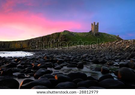 Dramatic sunrise at Dunstanburgh Castle - stock photo