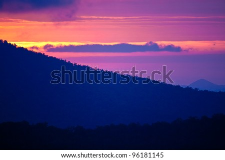 Dramatic sunrise of purple, orange and pink over the blue ridge mountains - stock photo