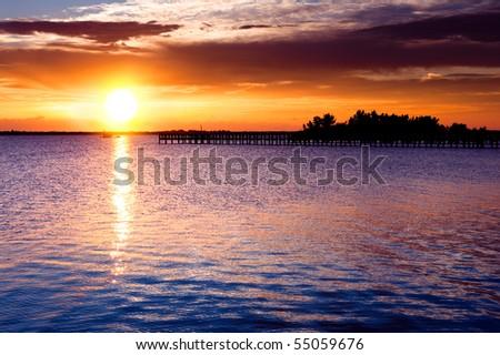 Dramatic sunrise over river pier. Indian river, Florida, USA - stock photo