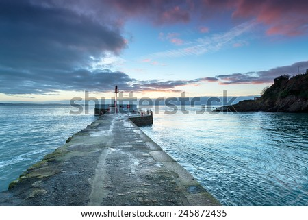 Dramatic sunrise over the pier at Looe on the south coast of Cornwall - stock photo