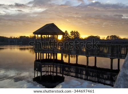Dramatic sunrise shown through a gazebo on a lake.
