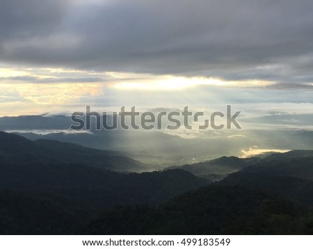 Dramatic sunset and sunrise sky with flare and the sun goes up or down behind silhouette of cloud and mountain layer
