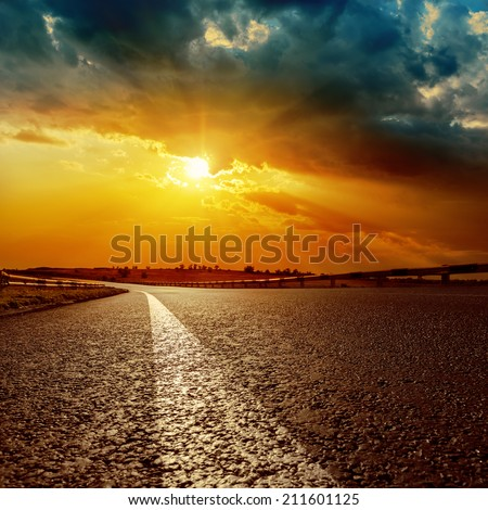 dramatic sunset and white line on asphalt road to horizon - stock photo