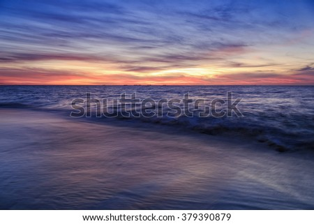 dramatic sunset at Cottesloe beach in Perth, Western Australia. Incoming wave flowing on wet sand under setting sun and clouds.