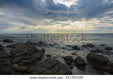 Dramatic sunset at the ocean with boulder rocks - stock photo