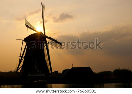 Dramatic sunset behind a windmill showing a silhouette.