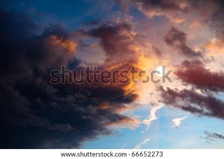 Dramatic sunset clouds surrounding sun. - stock photo