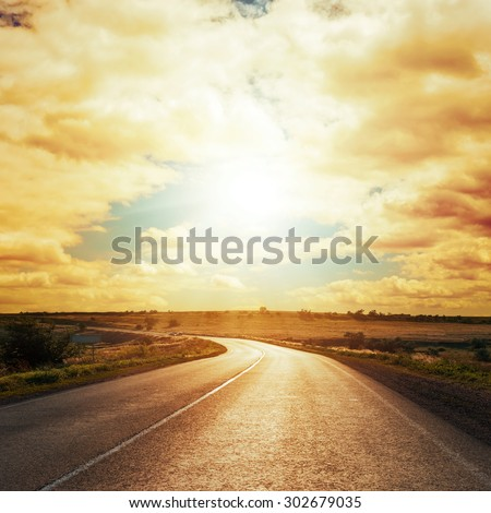 dramatic sunset in clouds over asphalt road - stock photo
