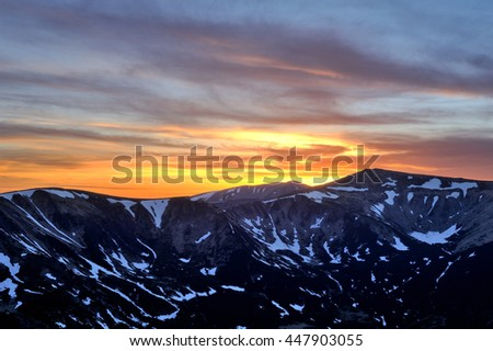 Dramatic sunset in the mountains. Vivid yellow and blue sky with huge clouds and mountains silhouettes covered with melting snow. Carpathian mountains, Ukraine